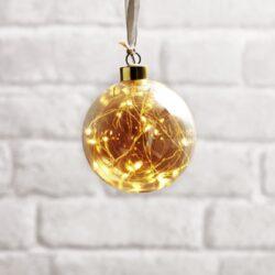 Koule Glow zlatá 10 cm x 11 cm-Skleněná vánoční dekorace na zavěšení s LED podsvícením. Baňky jsou spojeny především s Vánocemi, ale při správném použití v interiéru mohou být i celoroční ozdobou. Baňka je napájena bateriemi přes bateriový box na konci kabelu. Uvnitř je tenký drát DEW DROP s mikroLED, které dodávají neuvěřitelně teplou barvu a jemné, romantické světlo.