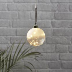 Koule Glow mléčná 10 cm x 11 cm-Skleněná vánoční dekorace na zavěšení s LED podsvícením. Baňky jsou spojeny především s Vánocemi, ale při správném použití v interiéru mohou být i celoroční ozdobou. Baňka je napájena bateriemi přes bateriový box na konci kabelu.  Uvnitř je tenký drát DEW DROP s mikroLED, které dodávají neuvěřitelně teplou barvu a jemné, romantické světlo.
