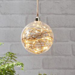 Koule Glow průhledná 14 cm x 15 cm-Skleněná vánoční koule k zavěšení s LED podsvícením. Vánoční koule napájená zdrojem s 3metrovým kabelem. Uvnitř tenký drát DEW DROP s mikroLED, které dodávají neuvěřitelně teplou barvu a jemné, romantické světlo. Baňky jsou spojeny především s Vánocemi, ale při správném použití v interiéru mohou být i celoroční ozdobou.